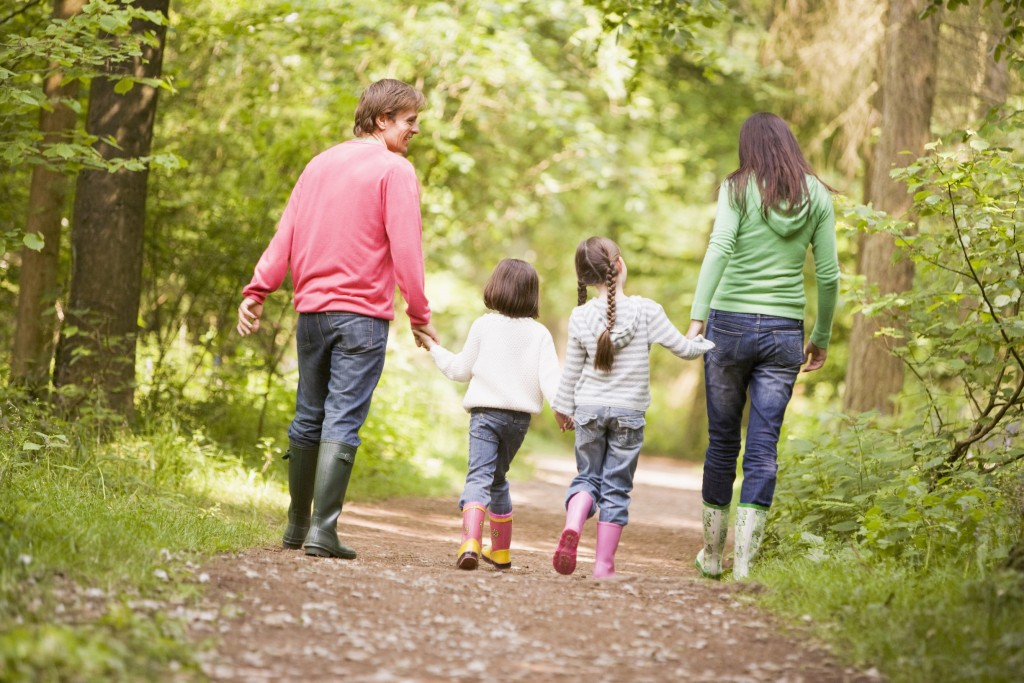 Family walking on path holding hands